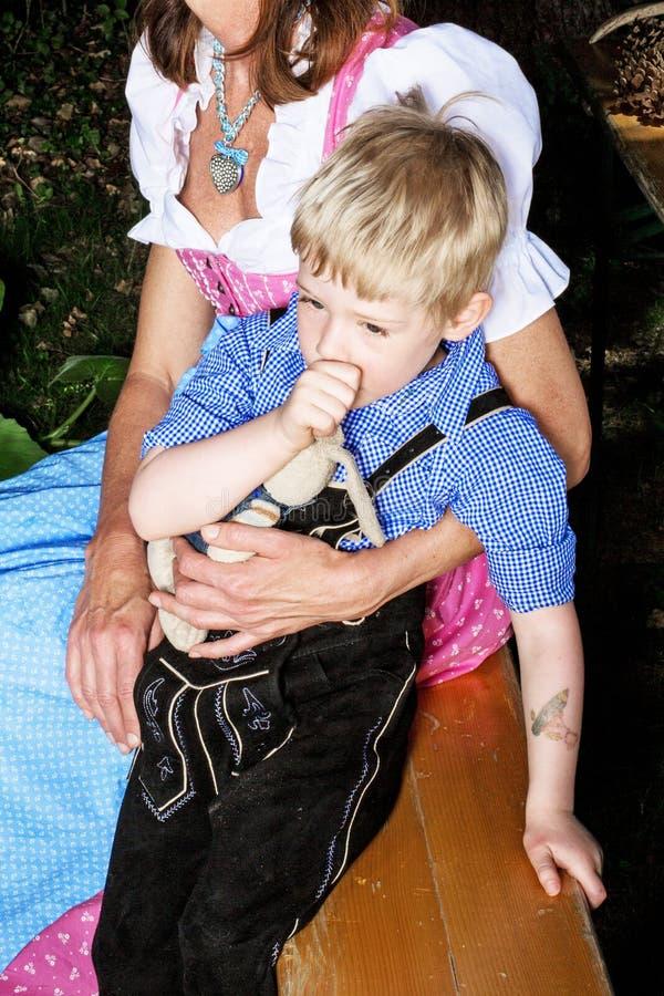 Bayerischer Junge mit der Mutter, die auf Bank an sitzt, beergarden lizenzfreie stockfotos