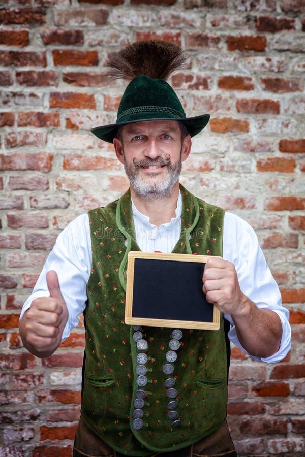 Bayerischer Mann, der ein schwarzes Brett und Daumen hochhält lizenzfreie stockbilder
