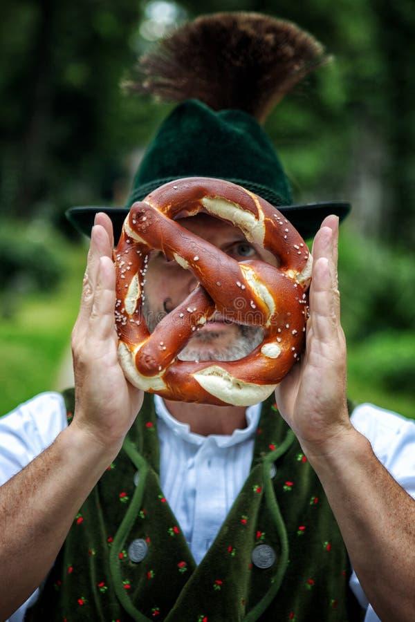Bayerischer Mann, der eine Brezel vor seinem Gesicht hält lizenzfreie stockbilder