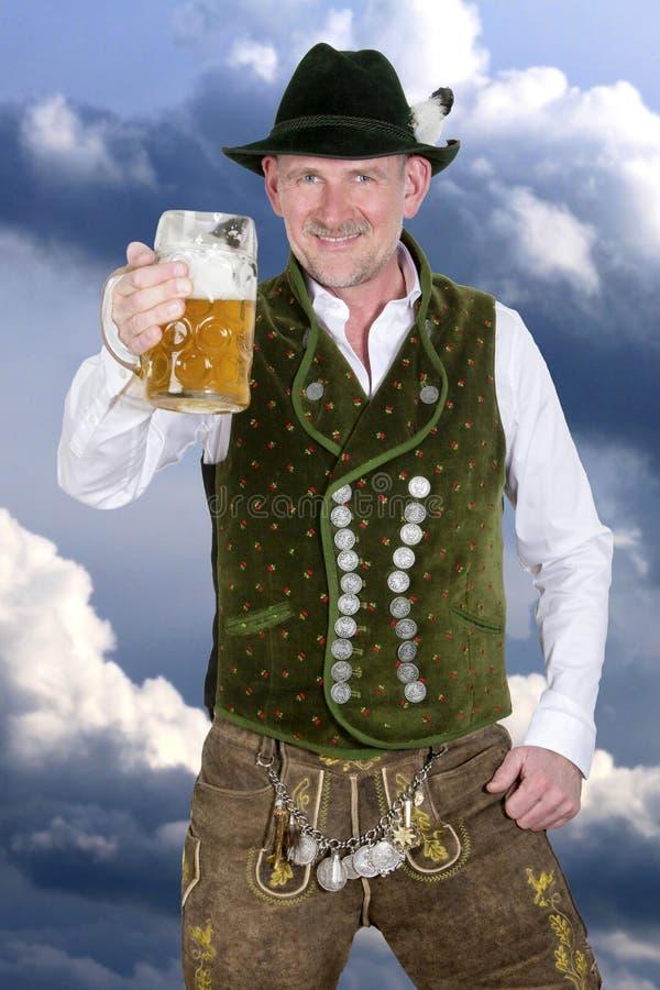 Bayerischer Mann, der einen Becher Bier hält stockfoto