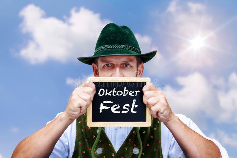 Bayerischer Mann, der schwarzes Brett mit dem Wort Oktoberfest hält lizenzfreies stockfoto