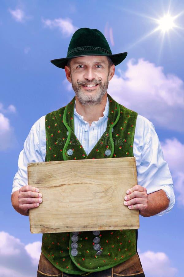 Bayerischer Mann, der unter blauem Himmel steht und hölzerne Planke hält lizenzfreies stockfoto