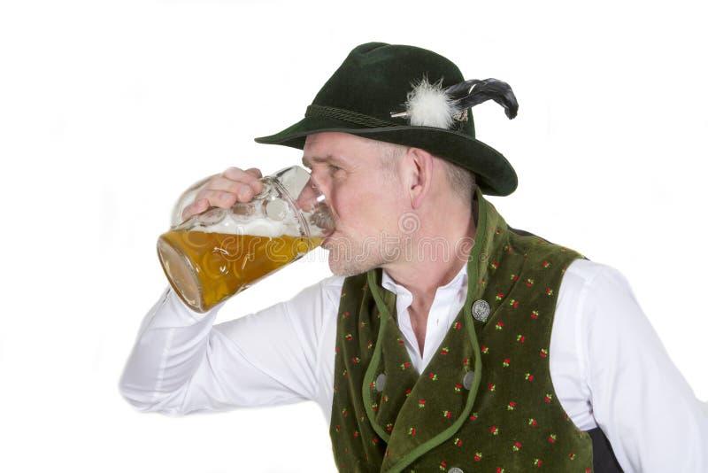 Bayerischer Mann, der von einem Becher Bier trinkt lizenzfreies stockfoto