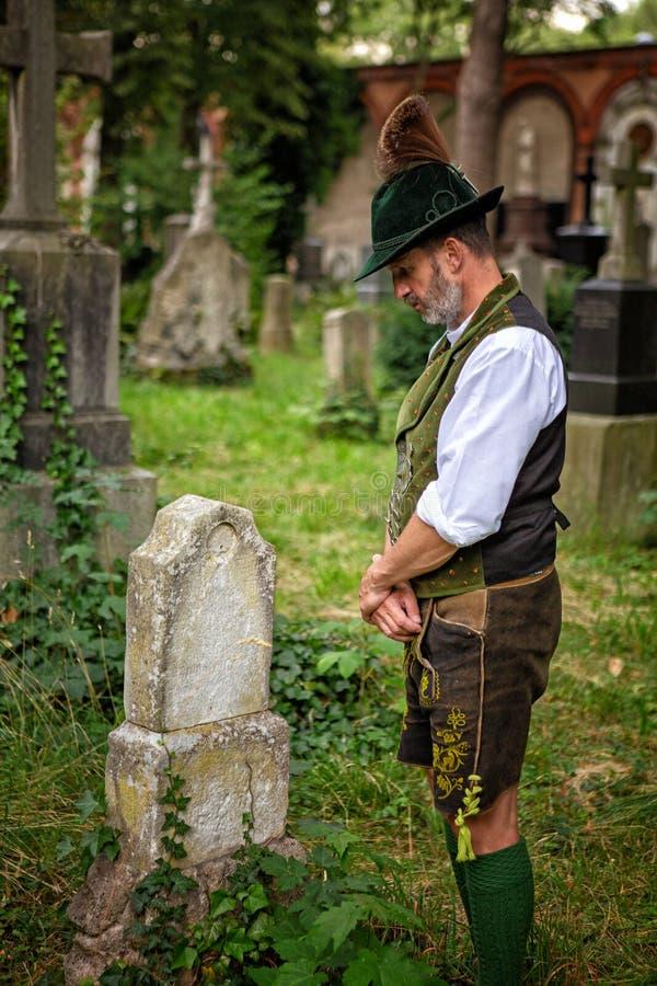 Bayerischer Mann, der vor Grab steht lizenzfreies stockbild