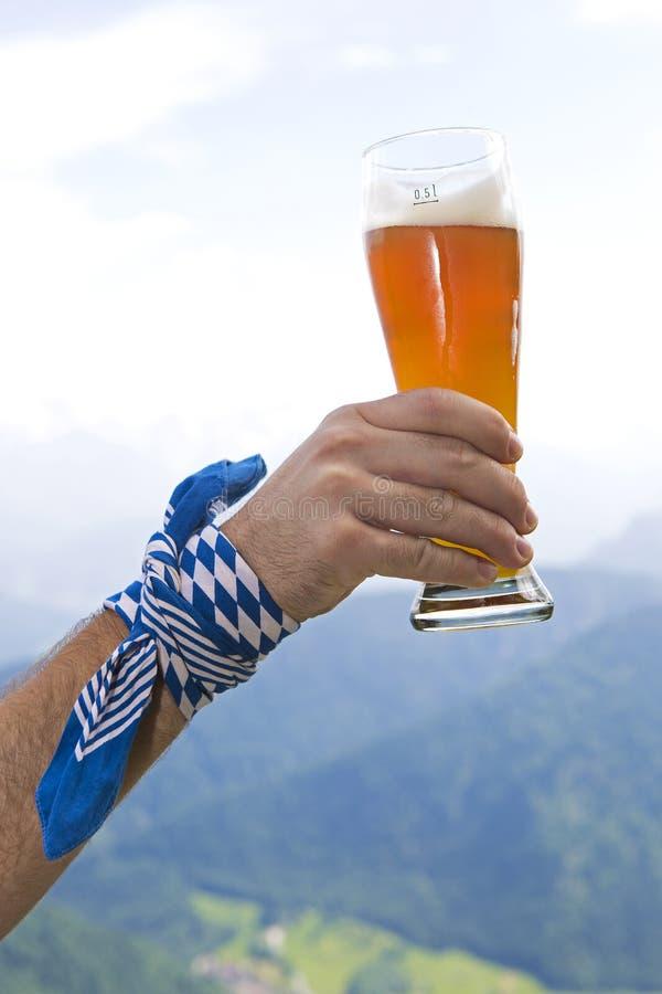 Bayerischer Mann, der Weizenbierglas in der Luft hält stockfotografie