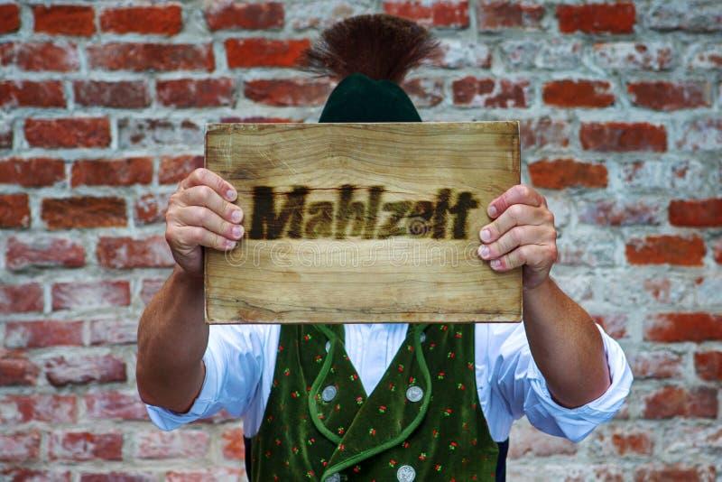 Bayerischer Mann, der Zeichen mit dem deutschen Wort für guten Appetit hält lizenzfreies stockbild