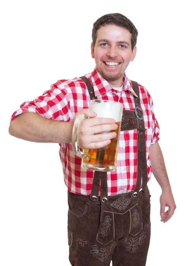 Bayerischer Mann mit den ledernen Hosen, die Bierkrug zeigen lizenzfreie stockbilder