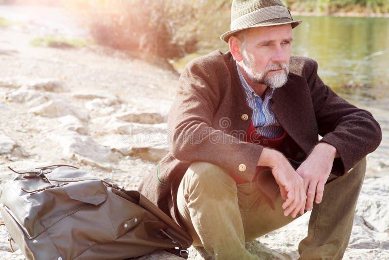 Bayerischer Mann in seinem 50s, das durch den Fluss sitzt lizenzfreies stockbild