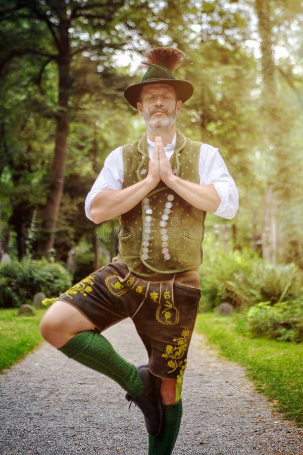 Bayerischer in Yogaposition stehender und meditierender Mann stockfotos