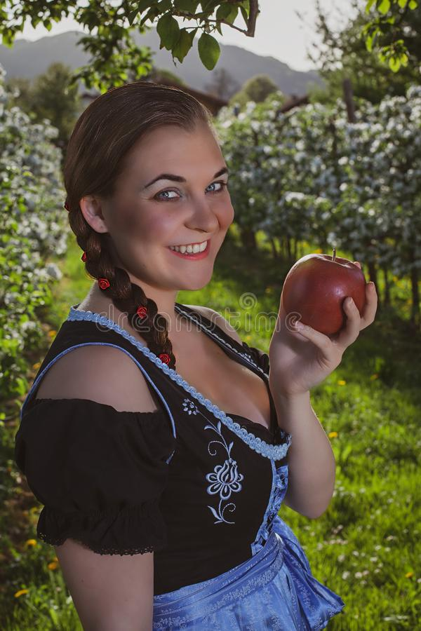 Bayerisches Mädchen mit Apple lizenzfreie stockbilder