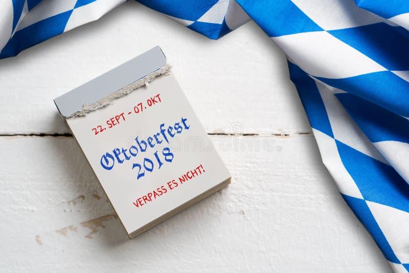 Bayersk bordduk på träbakgrund och en reva-avkalender med slogan`-Oktoberfest 2018 `, royaltyfria bilder