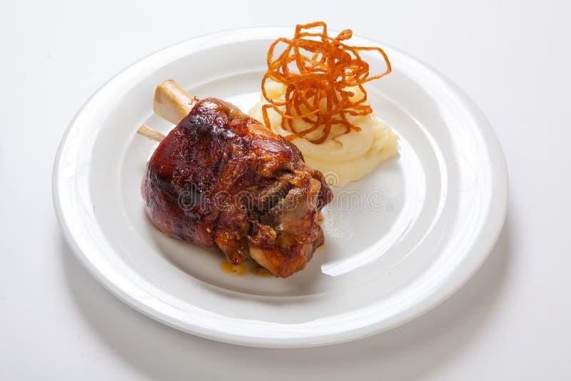 Bayersk grillad knoge av griskött och mosade potatisar på ljus bakgrund arkivbild