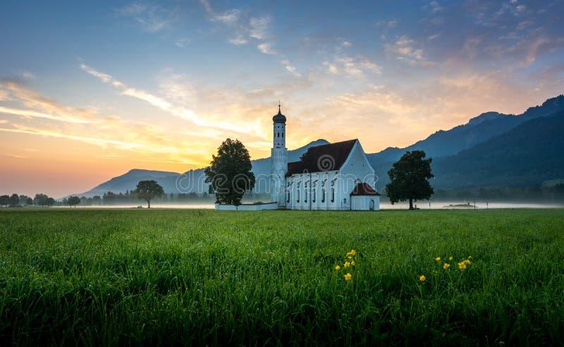 Bayersk kyrka i bavarian fjällängar på soluppgång arkivfoto
