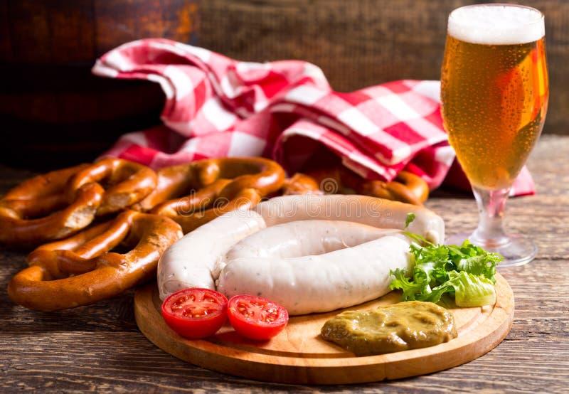 Bayerska vita korvar med kringlan och exponeringsglas av öl royaltyfri bild