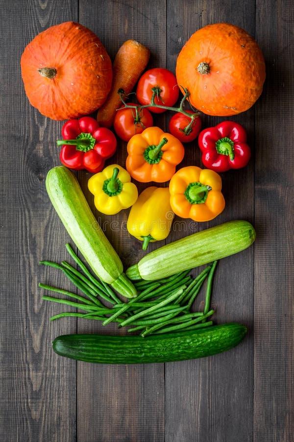 Baza zdrowa dieta Warzywa banie, papryka, pomidory, marchewka, zucchini na ciemnego drewnianego tła odgórnym widoku zdjęcie royalty free