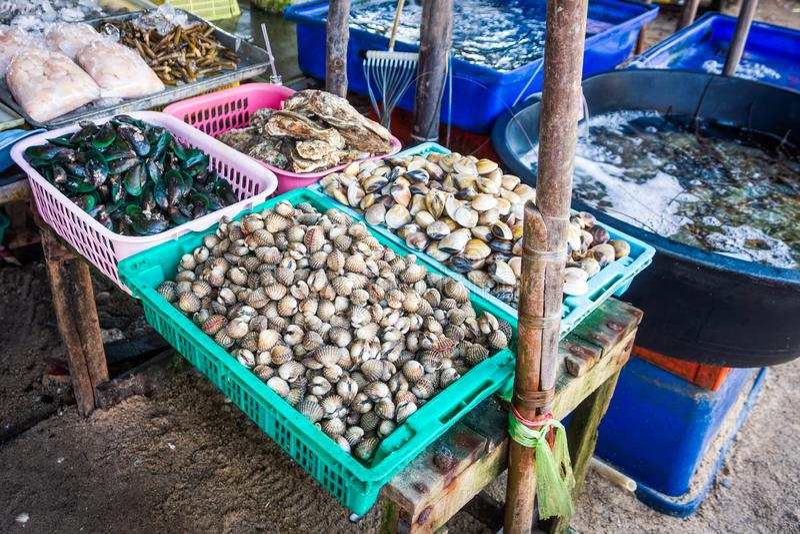 Bazar tailandês com variedade de moluscos, de mexilhões e de marisco frescos nas cestas e nos tanques imagens de stock