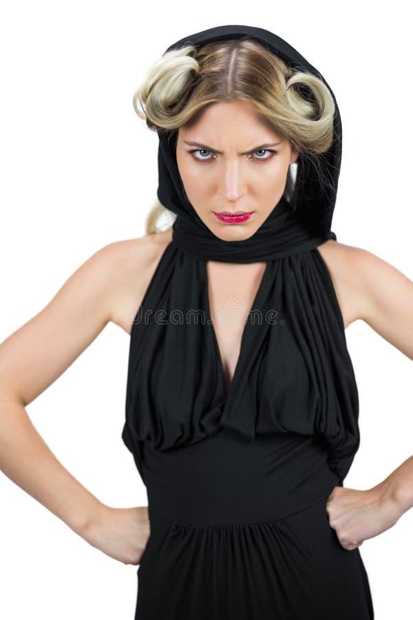 Bazig griezelig blonde die het zwarte kleren fronsen dragen stock foto's