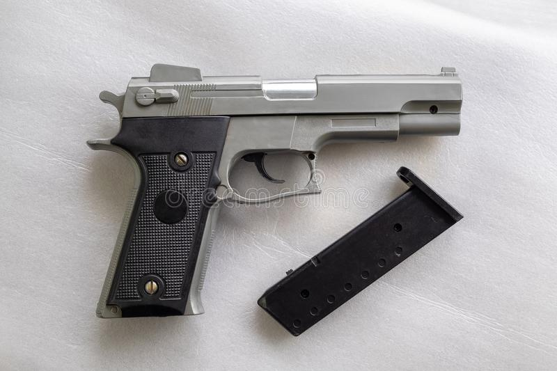 BB Gun, Old Airsoft Pistol Toy and Magazine with BB Gun Bullets on White Foam Background stock photos