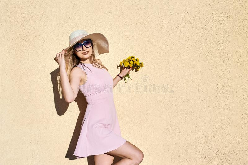 Bbeautiful, beau, fille dans une robe rose, dans un sourire de chapeau de paille, posant le portrait contre un mur jaune image stock