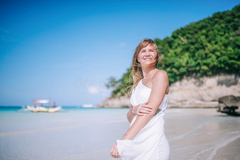Bbeautiful blond long hair woman in white dress dancing on the beach. Happy island lifestyle. royalty free stock images