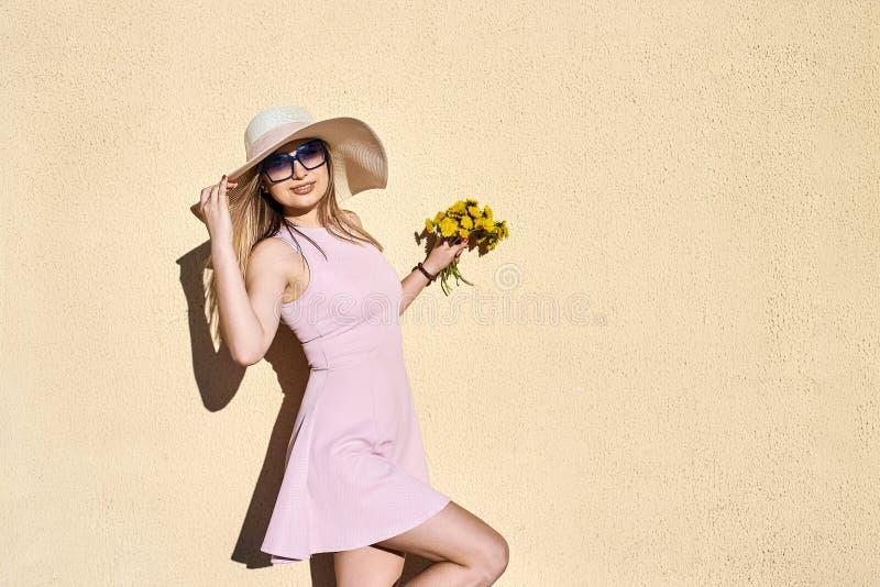 Bbeautiful, reizend, Mädchen in einem rosa Kleid, in einem Strohhutlächeln, Porträt gegen eine gelbe Wand aufwerfend stockbild