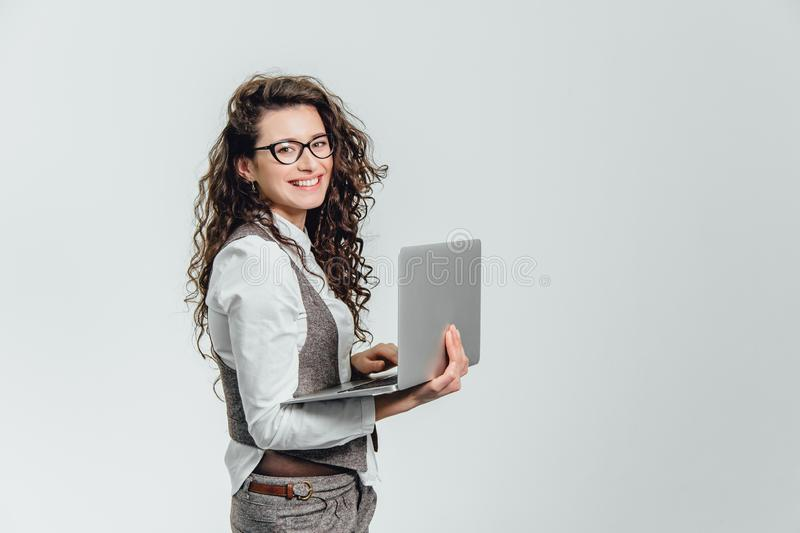 BBeautiful young girl smiles. Works on a laptop in glasses and a white shirt stock photo