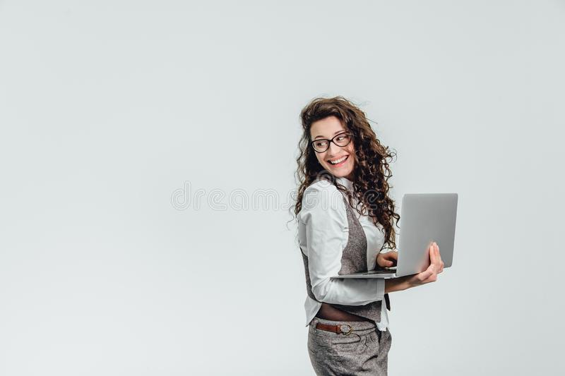 BBeautiful young girl smiles. Works on a laptop in glasses and a white shirt stock photos