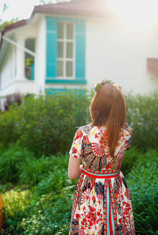 BBeautiful young red-haired woman in a bright dress standing in nature, looking at the windows royalty free stock photos