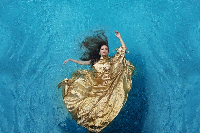 Bbeautiful young woman in gold dress, evening dress floating weightlessly elegant floating in the water in the pool royalty free stock photos