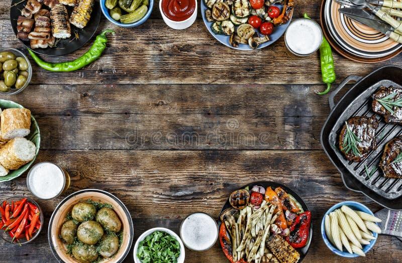 BBG som grillas, grönsaker, biffar, potatisar, sallad, mellanmål, öl royaltyfria foton
