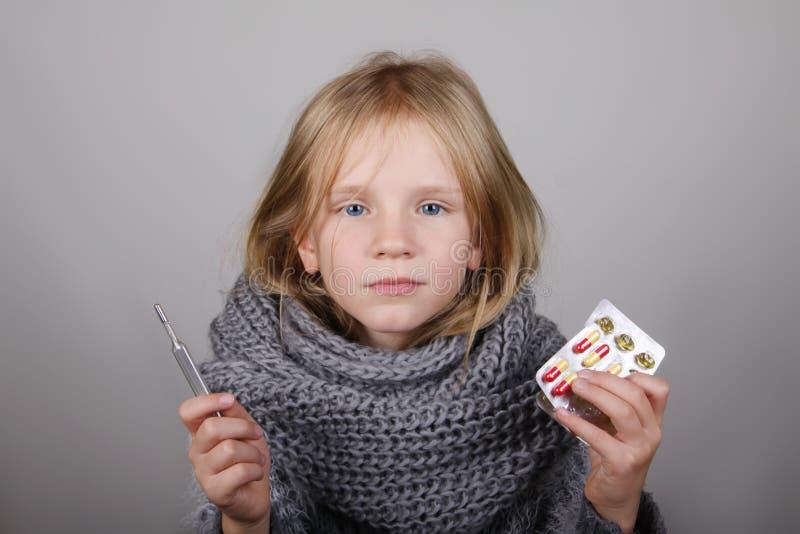 Bblond małej dziewczynki mienia włosiana medycyna i termometr w ręce dziecko jest chore Dziecko zimy opieki zdrowotnej grypowy po fotografia stock