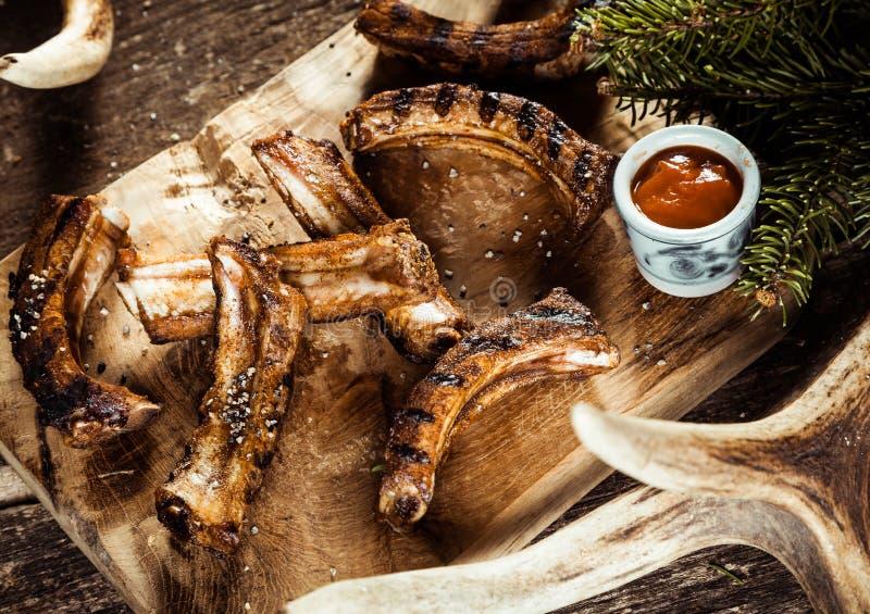 BBQ在木板供食的鹿肉排骨 库存照片