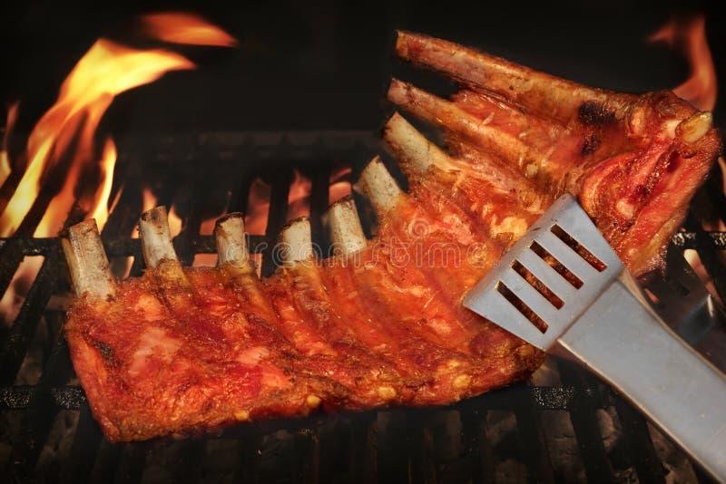BBQ在热的火焰状格栅的烤婴孩后面猪排 免版税图库摄影