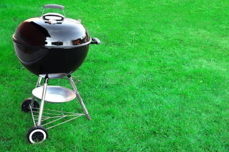 BBQ木炭在草坪背景的格栅装置与拷贝Sp 免版税库存图片