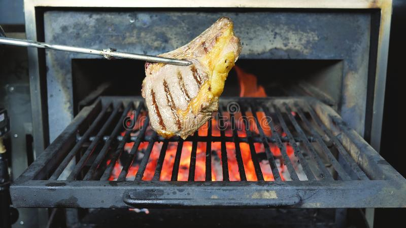 Bbq σάλτσα στο βόειο κρέας σε μια μπριζόλα σχαρών υπαίθρια Κλείστε αυξημένος ψημένης στη σχάρα της φλόγα BBQ Τ μπριζόλας βόειου κ στοκ φωτογραφία με δικαίωμα ελεύθερης χρήσης