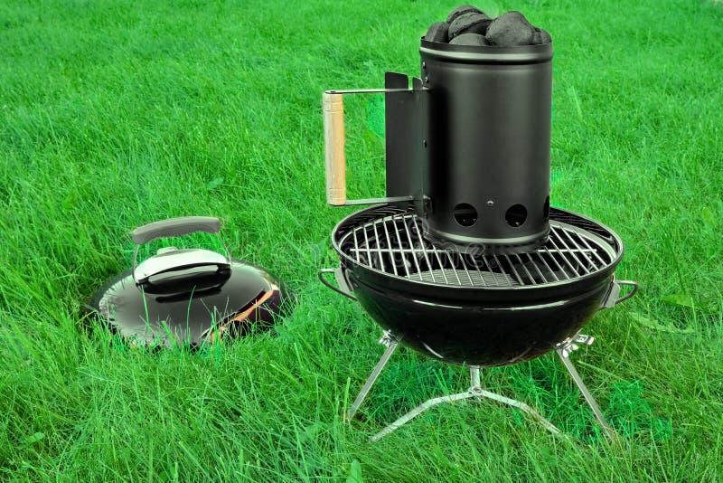 BBQ σχάρα κατσαρολών με τον εκκινητή ανθρακόπλινθων ξυλάνθρακα στο χορτοτάπητα στοκ εικόνες