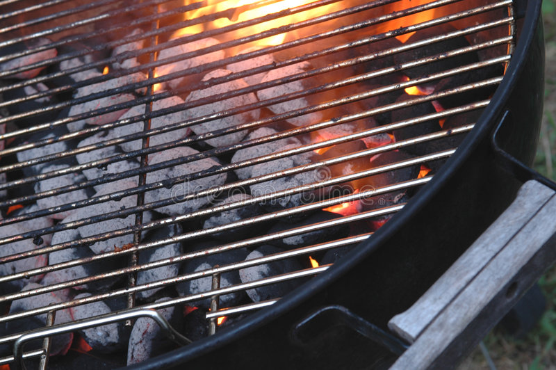 Bbq barbecue briquette flames through the grid. A hot charcoal briquette barbecue grill flames in the summertime royalty free stock photography