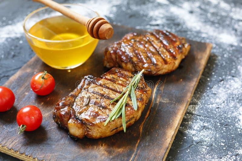 BBQ, bifteks grillés, romarin, miel, planche à découper en bois, préparation de dîner, plan rapproché copiez l'espace, foyer séle photographie stock libre de droits