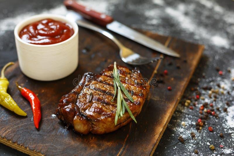 BBQ, bifteks grillés, romarin, planche à découper en bois, préparation de dîner, plan rapproché copiez l'espace, foyer sélectif, photos libres de droits