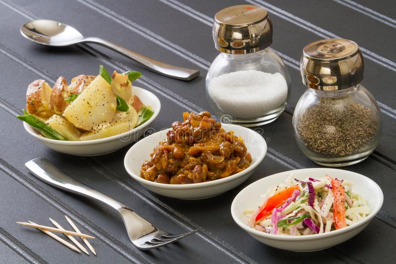 BBQ Boczni naczynia na czerń stole z rozwidleniem, łyżką, solą, pieprzem i wykałaczkami, fotografia royalty free