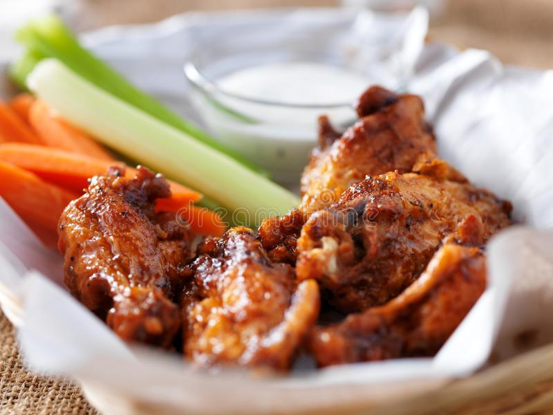 Bbq buffalo chicken wings in basket, with ranch dip, carrot and celery sticks royalty free stock image