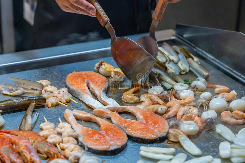 BBQ chef frying assortment of seafood in buffet restaurant. BBQ chef frying assortment of seafood in buffet meal restaurant royalty free stock photos