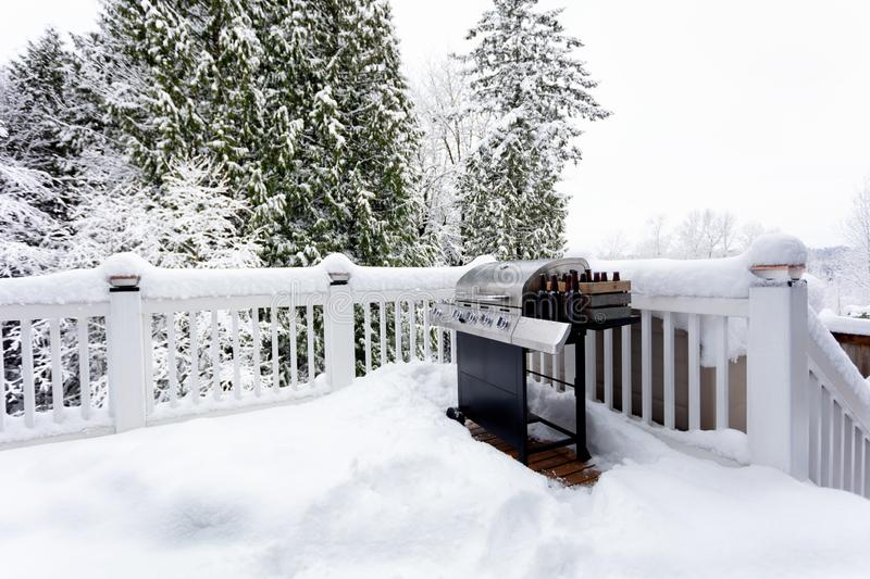 BBQ cooker with beer during winter time on home outdoor deck. BBQ cooker with bottles of beer during winter time on home outdoor deck royalty free stock photos