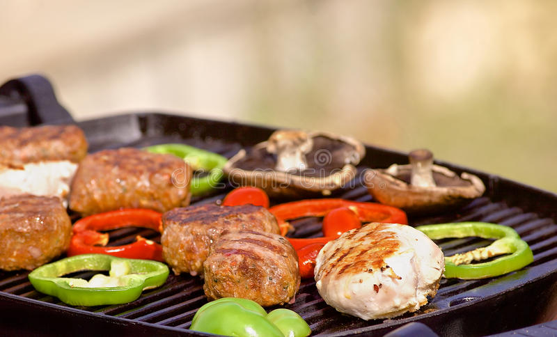 BBQ cooking with chicken mushroom and peppers. Australian or american BBQ on a grill with sausages, red pappers and mushrooms royalty free stock photography