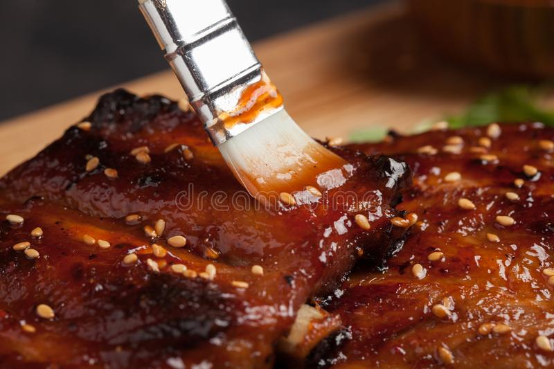 BBQ de propagation de sauce à chef en gros plan sur des nervures avec la brosse photos libres de droits