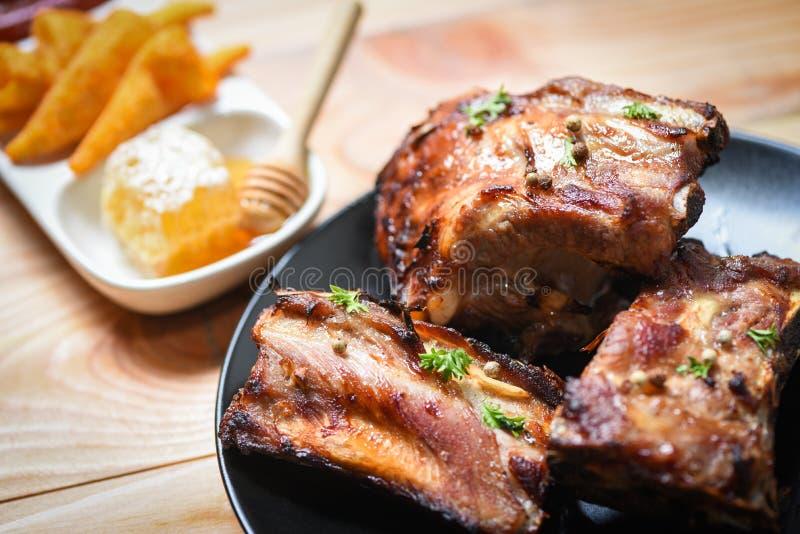 Bbq de varkensvleesribben met honings zoete saus worden geroosterd en de kruidenkruiden dienden op de lijst - Geroosterd gesneden stock afbeelding