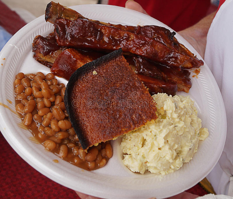 BBQ Dinner. Competitive BBQ competition plate. Cornbread, ribs, baked beans, and potato salad stock image
