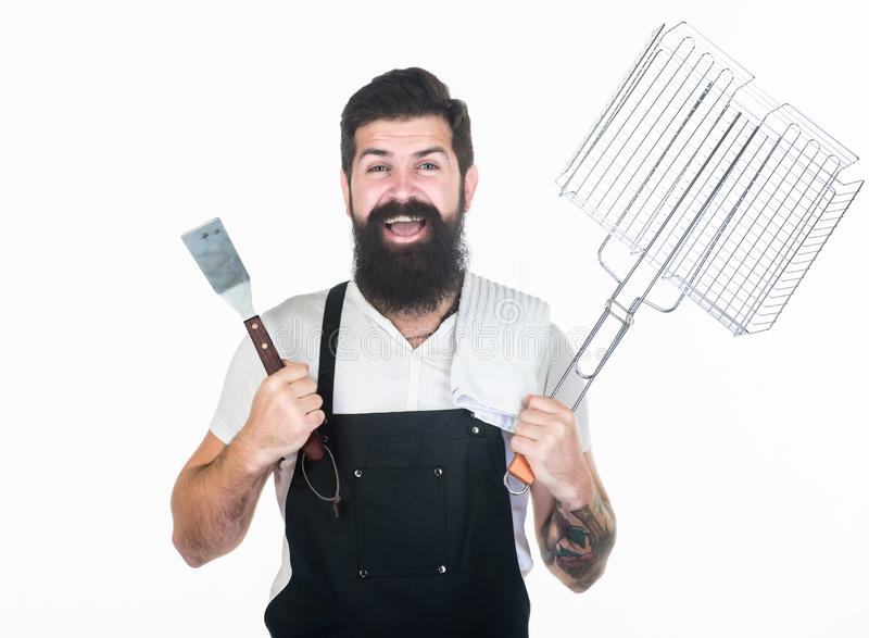 BBQ is a feast. Cook holding portable grilling basket and spatula. Bearded man with barbecue grilling tools in hands. Happy hipster using metal grilling stock images