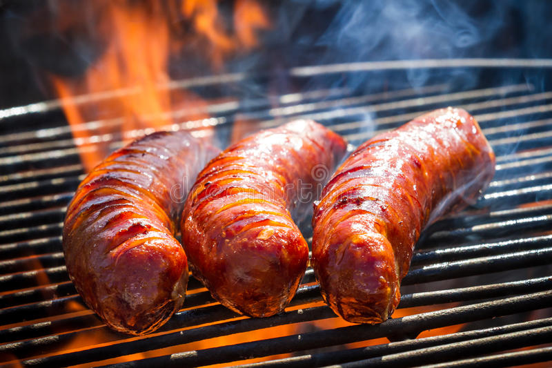 BBQ with fiery sausages on the grill stock images