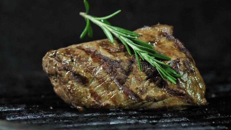 BBQ fillet of beef fried on coals with a sprig of rosemary on top. BBQ fillet of beef fried on coals with a sprig of rosemary top close-up stock image